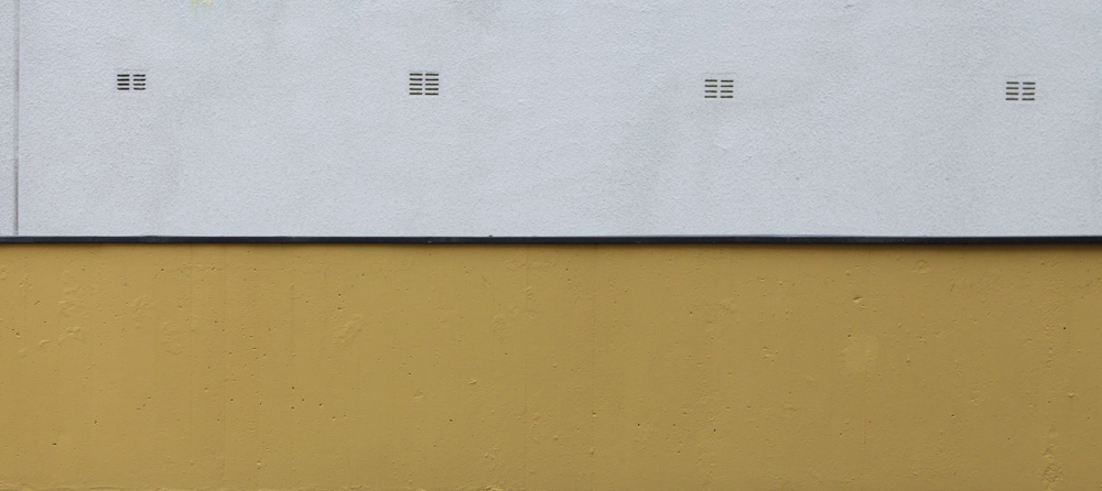 minimalistic horizontal image, seeming two-dimensional, showing a white wall with 4 geometric slits behind a yellow wall