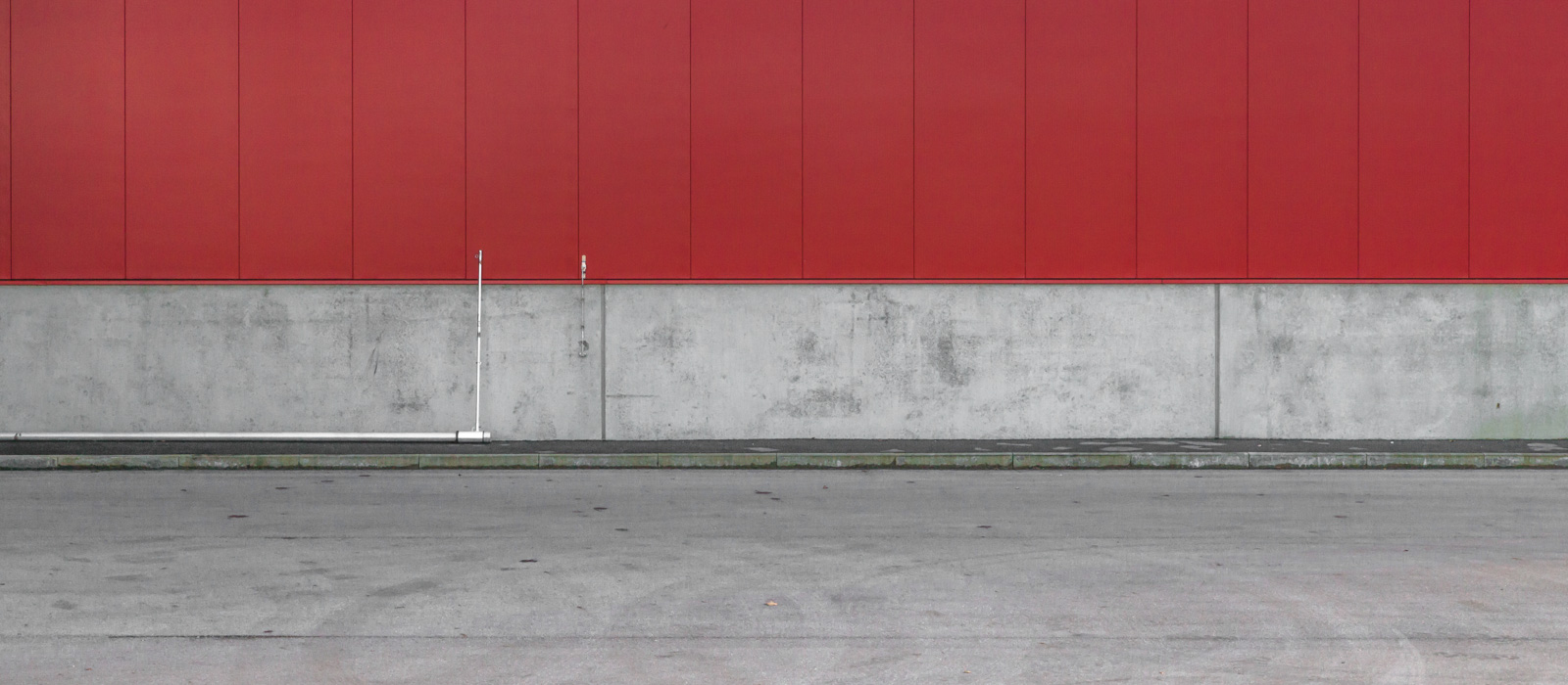 minimalistic horizontal image, seeming two-dimensional, showing a red steel wall with a concrete socket, a pedestrians walk and a street