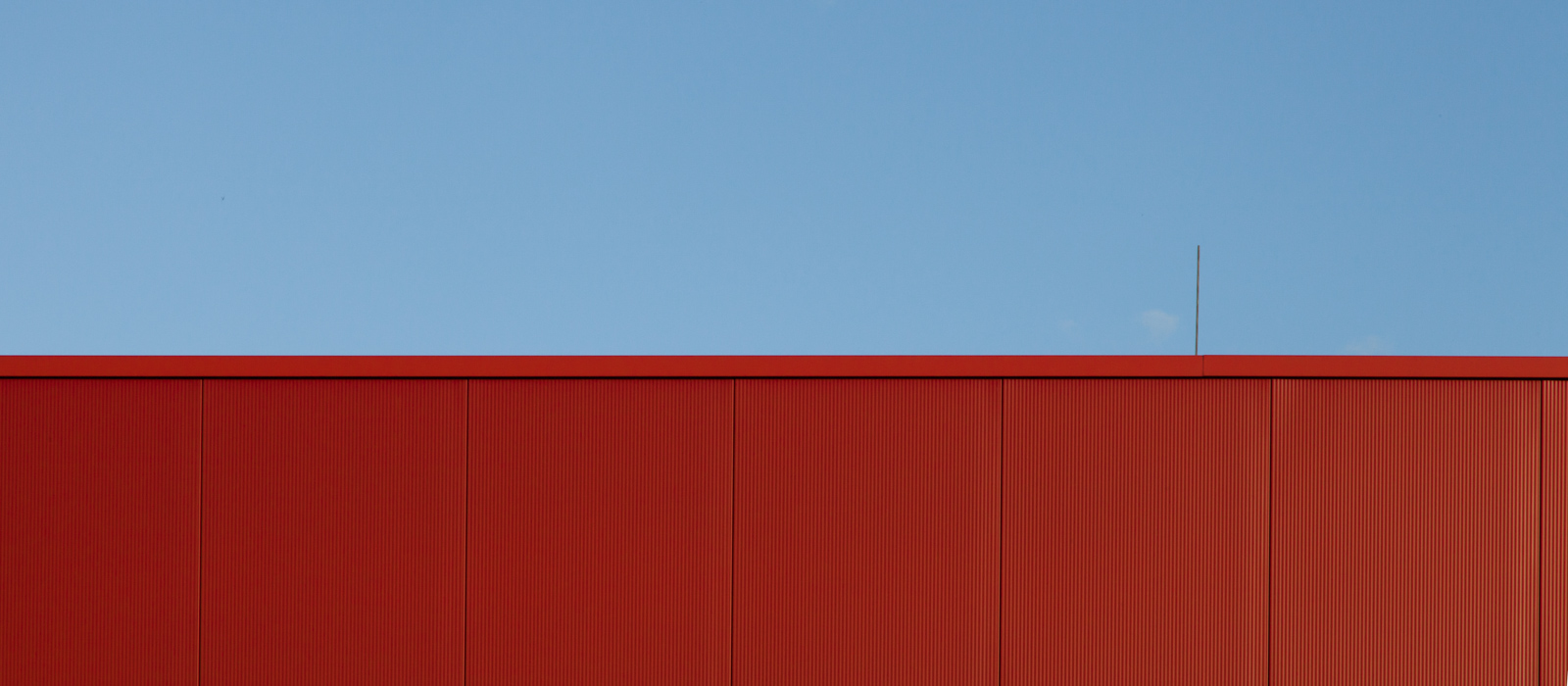 minimalistic horizontal image, seeming two-dimensional, showing a red steel wall with an antenna against the blue sky