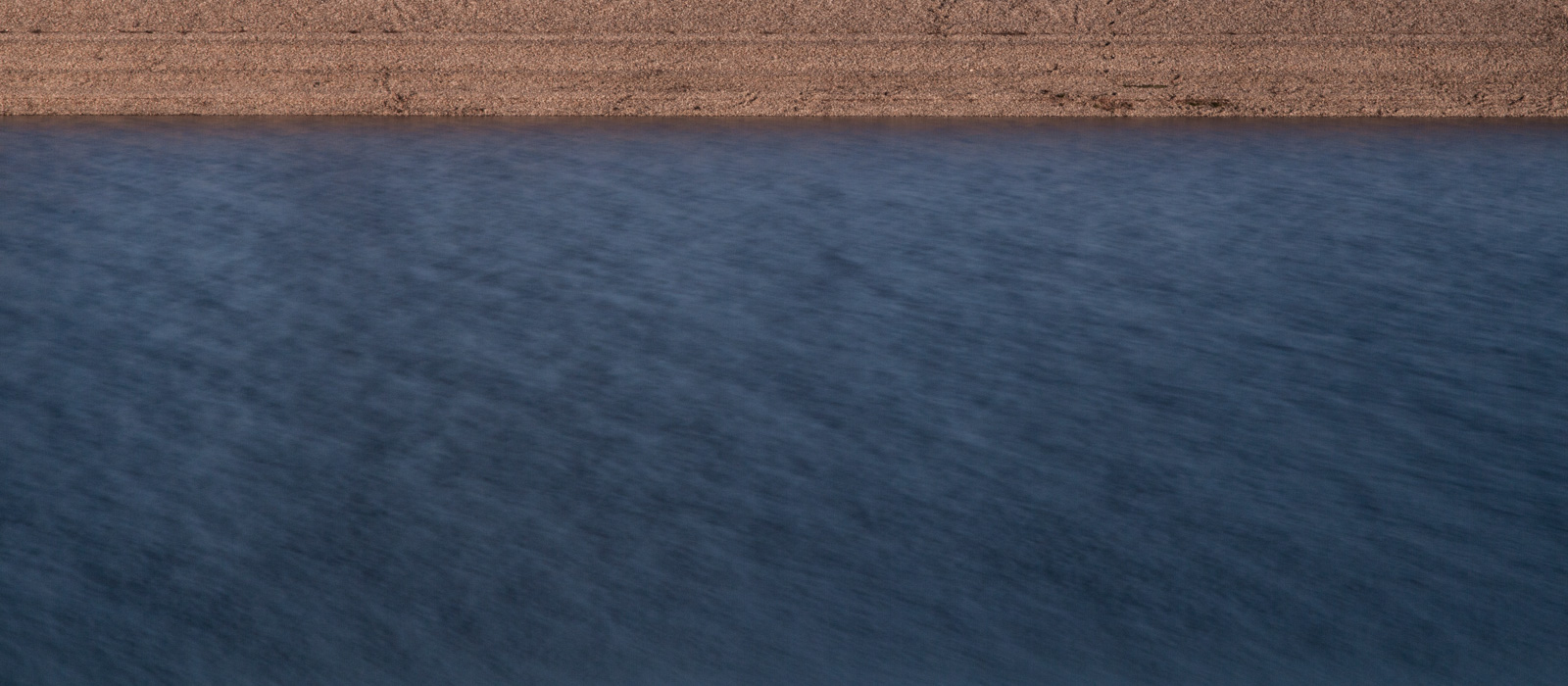 minimalistic horizontal image, seeming two-dimensional, showing a pebble beach and water with a smooth gradient from bright to dark blue and slight blur due to aperture