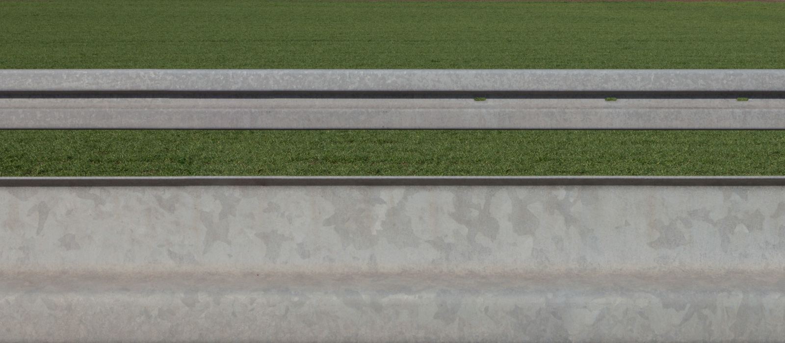 minimalistic horizontal image, showing two guardrails against grass – letting them seem two-dimensional