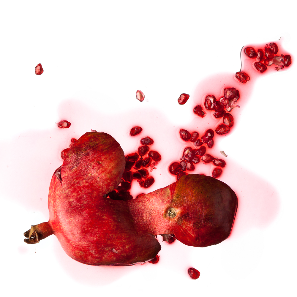 a minimalistic picture aesthetically showing a smashed grenadine fruit on pure white ground (no shadow)