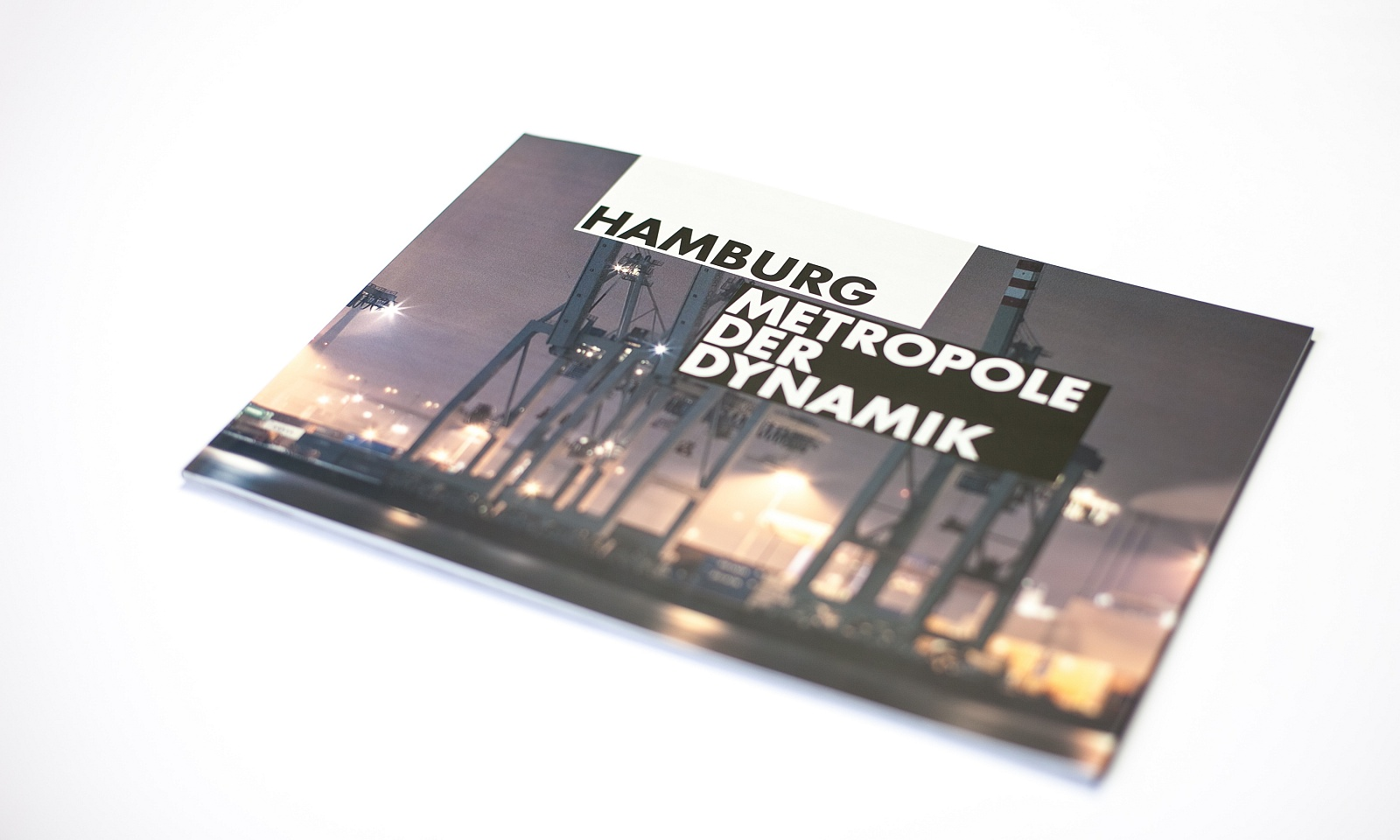 "a photo of a closed brochure ""hamburg – metropole of dynamic"", cover picture shows cranes in the harbor"