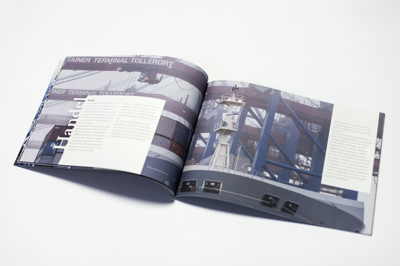 open brochure, showing two text fields and a large image of cranes loading a huge transport ship