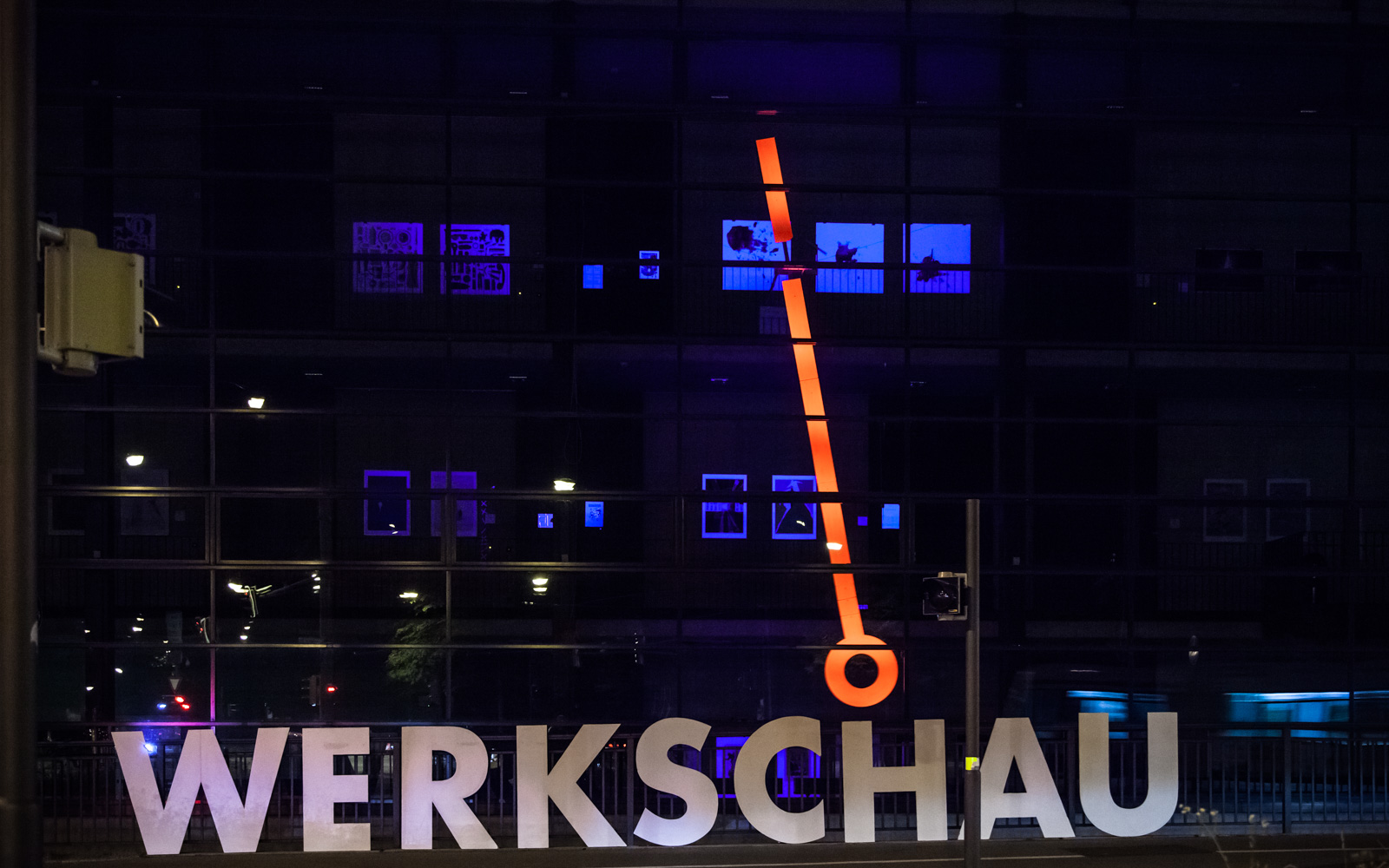 "a short exposure shot at night where only the ""werkschau"" word and the pendulum can be seen"
